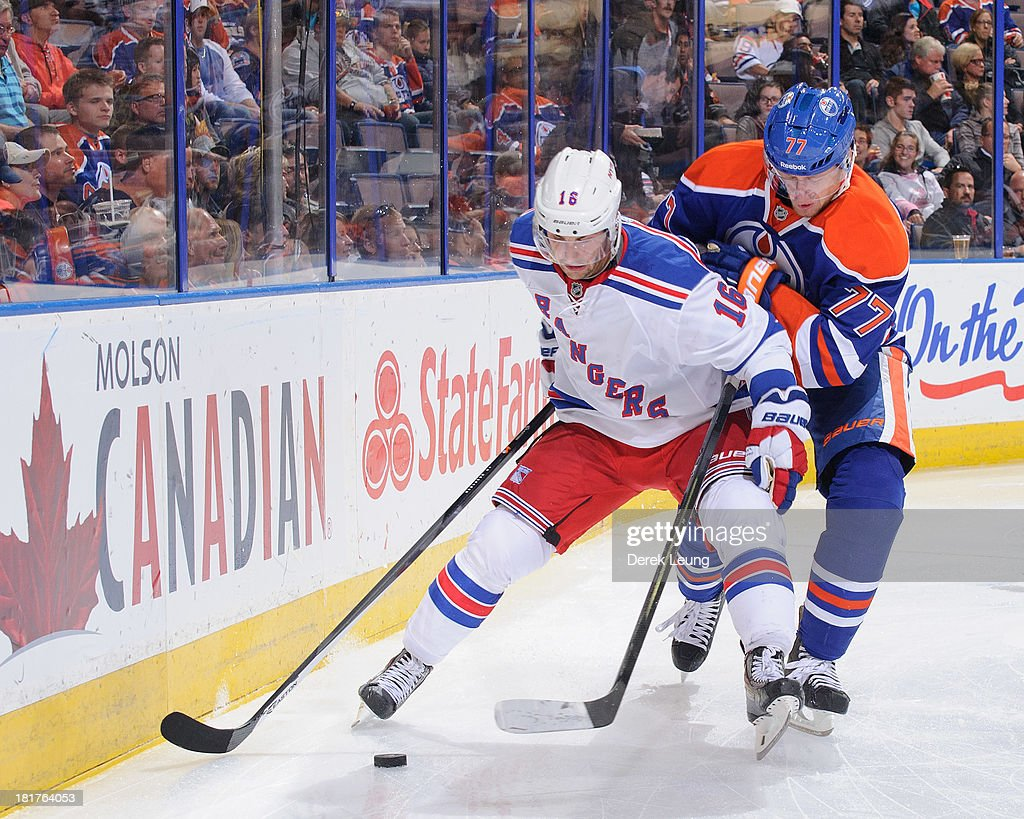 Anton Belov #77 of the Edmonton Oilers tries to check Derick Brassard #16 of the New York Rangers during a preseason NHL game at Rexall Place on September 24, 2013 in Edmonton, Alberta, Canada.