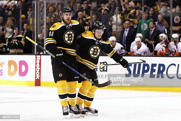 Anton Blidh of the Boston Bruins celebrates with Jimmy Hayes after scoring his first NHL goal against the New York Islanders during the third period...