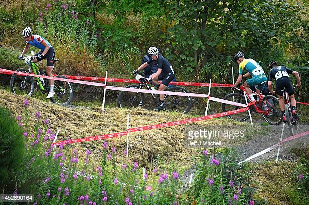 Anton Cooperof New Zealand looks over his shoulder at Daniel McConnell of Australia compete in the Mountain Biking at Cathkin Braes Mountain Bike...