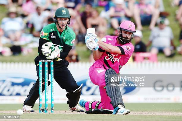 Anton Devcich of the Knights bats as Dane Cleaver of the Stags looks on during the Super Smash Grand Final match between the Knights and the Stags at...