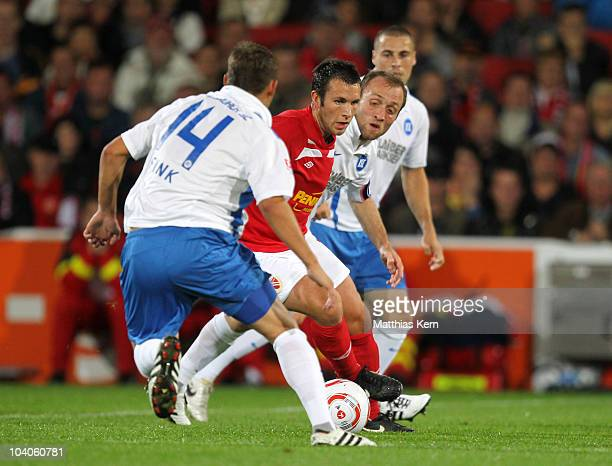Anton Fink, Marc Andre Kruska and Alexander Iashvili battle for the ball during the Second Bundesliga match between FC Energie Cottbus and Karlsruher...