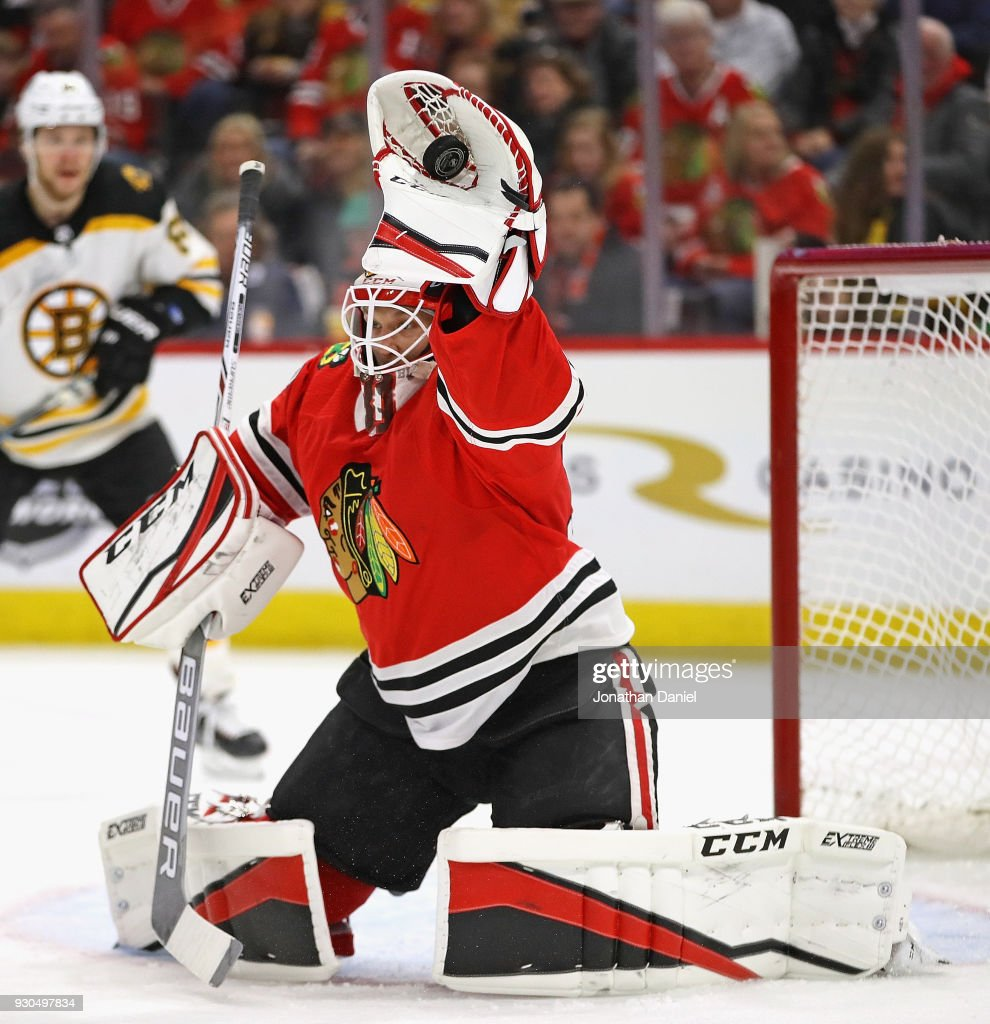Anton Forsberg #31 of the Chicago Blackhawks makes a glove save against the Boston Bruins at the United Center on March 11, 2018 in Chicago, Illinois.