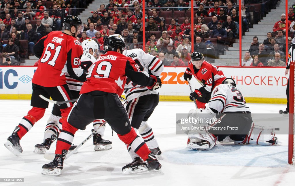 Anton Forsberg #31 of the Chicago Blackhawks makes a save against Ryan Dzingel #18 of the Ottawa Senators as Mark Stone #61 and Derick Brassard #19 of the Ottawa Senators look on in the second period at Canadian Tire Centre on January 9, 2018 in Ottawa, Ontario, Canada.