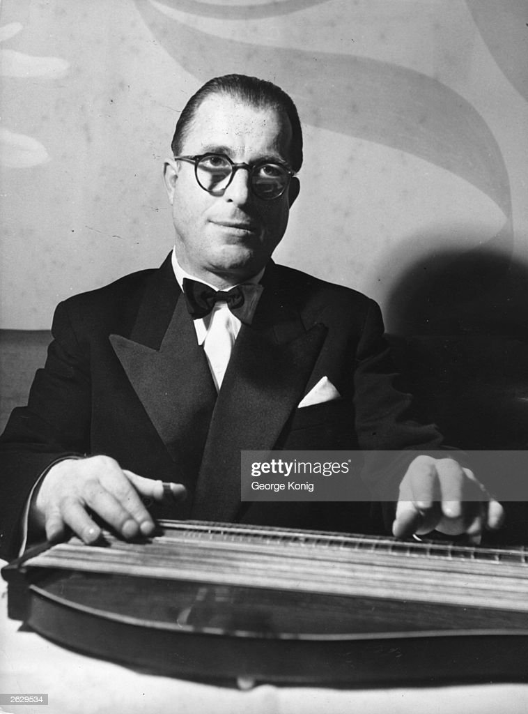 Anton Karas (1906 - 1985), composer of the famous score for the film 'The Third Man', playing his zither in London.