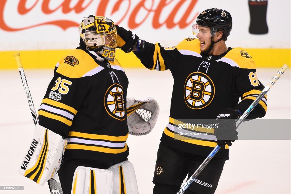 Anton Khudobin #35 and David Pastrnak #88 of the Boston Bruins celebrate a win against the Vancouver Canucks at the TD Garden on October 19, 2017 in Boston, Massachusetts.