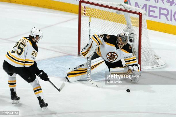 Anton Khudobin of the Boston Bruins goes to grab the puck as Brandon Carlo of the Boston Bruins skates during a NHL game against the San Jose Sharks...