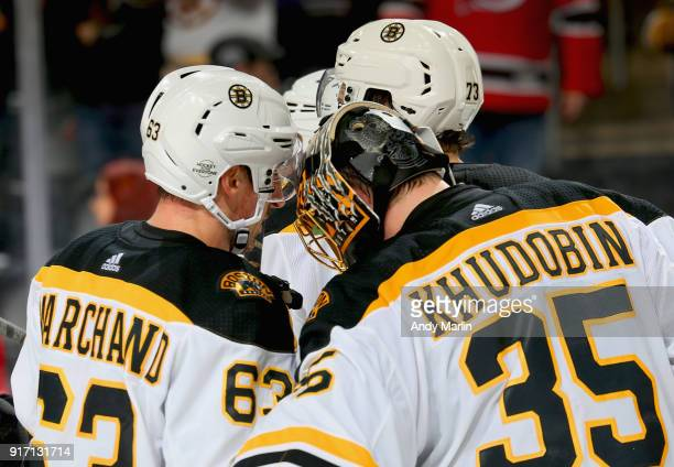 Anton Khudobin of the Boston Bruins is congratulated by Brad Marchand after defeating the New Jersey Devils at Prudential Center on February 11 2018...