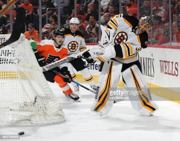 Anton Khudobin of the Boston Bruins shoots the puck from behind the net against Oskar Lindblom of the Philadelphia Flyers on April 1 2018 at the...