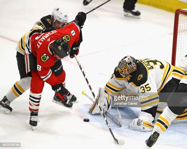 Anton Khudobin of the Boston Bruins stops a shot by Nick Schmaltz of the Chicago Blackhawks as Matt Grzelcyk applies pressure at the United Center on...