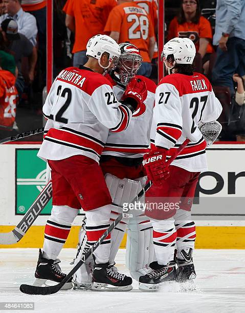 Anton Khudobin of the Carolina Hurricanes celebrates the win with teammates Manny Malhotra and Justin Faulk after the game against the Philadelphia...