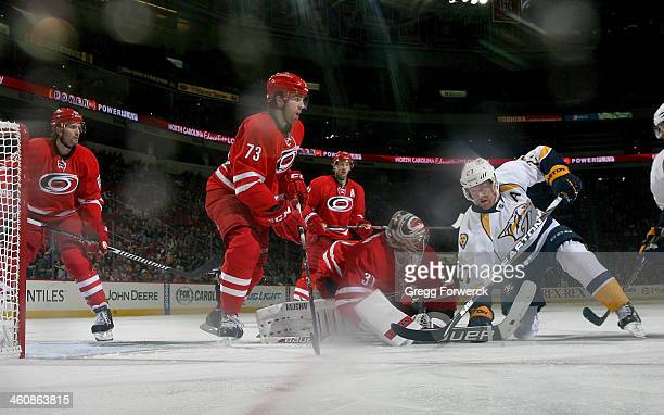 Anton Khudobin of the Carolina Hurricanes comes out of the crease to make a save as Patric Hornqvist of the Nashville Predators attempts to knock the...