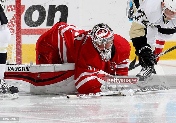 Anton Khudobin of the Carolina Hurricanes covers the puck during an NHL game against the Pittsburgh Penguins at PNC Arena on November 29 2014 in...