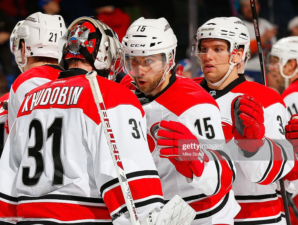 Anton Khudobin #31 of the Carolina Hurricanes is congratulated by teammates on their win against the New York Islanders at Nassau Veterans Memorial Coliseum on January 4, 2014 in Uniondale, New York. The Hurricanes defeated the Islanders 3-2.