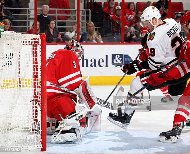 Anton Khudobin of the Carolina Hurricanes makes a save as Bryan Bickell of the Chicago Blackhawks skates into the crease during their NHL game at PNC...