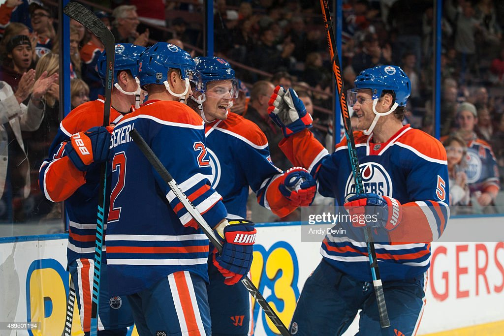 Anton Lander #51, Mark Fayne #5 and Andrej Sekera #2 of the Edmonton Oilers celebrate after a goal during a preseason game against the Calgary Flames on September 21, 2015 at Rexall Place in Edmonton, Alberta, Canada.