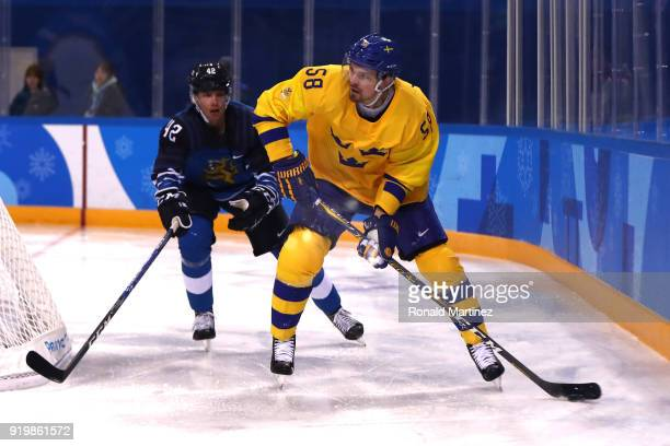 Anton Lander of Sweden controls the puck against Miro Heiskanen of Finland in the second period during the Men's Ice Hockey Preliminary Round Group C...