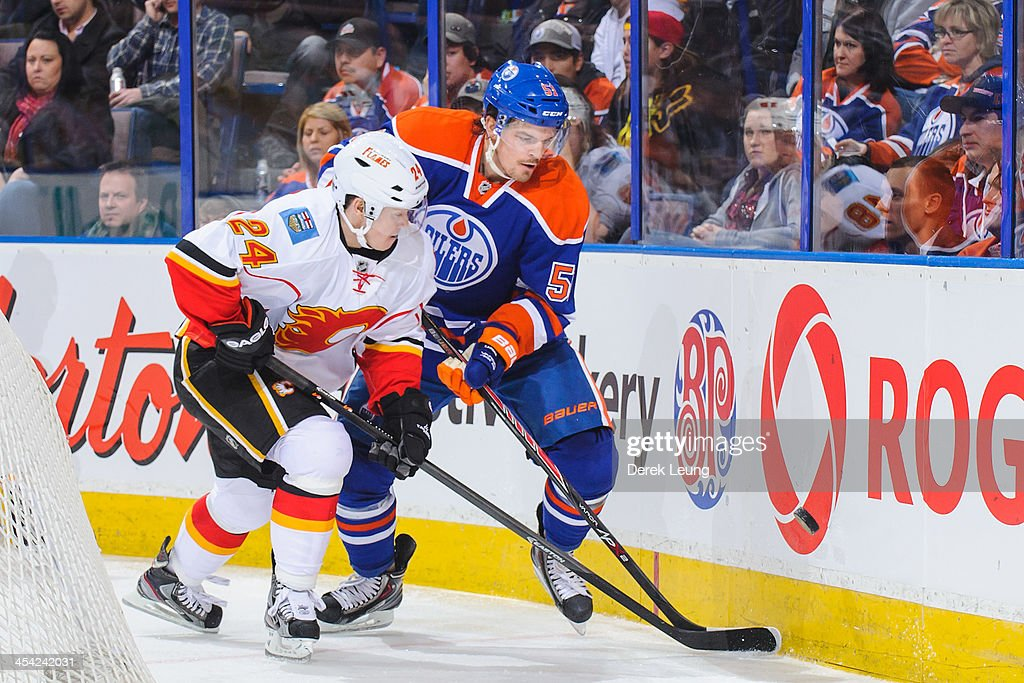 Anton Lander #51 of the Edmonton Oilers battles for the puck against Jiri Hudler #24 of the Calgary Flames during an NHL game at Rexall Place on December 7, 2013 in Edmonton, Alberta, Canada. The Flames defeated the Oilers 2-1 in overtime.