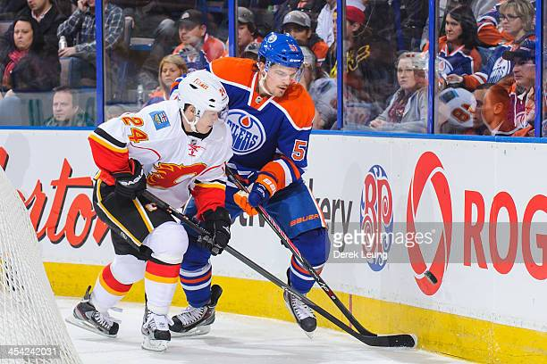 Anton Lander of the Edmonton Oilers battles for the puck against Jiri Hudler of the Calgary Flames during an NHL game at Rexall Place on December 7...