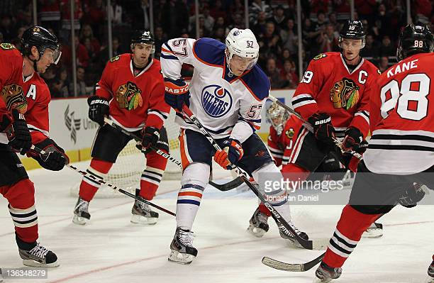 Anton Lander of the Edmonton Oilers controls the puck surrounded by Duncan Keith Nick Leddy Jonathan Toews and Patrick Kane of the Chicago Blackhawks...