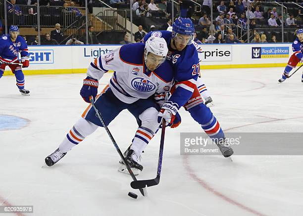 Anton Lander of the Edmonton Oilers is checked by Ryan McDonagh of the New York Rangers during the third period at Madison Square Garden on November...