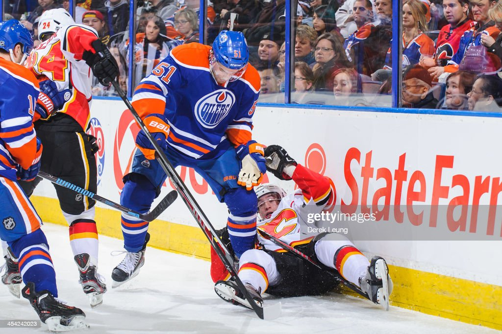 Anton Lander #51 of the Edmonton Oilers knocks Sven Baertschi #47 of the Calgary Flames off his feet during an NHL game at Rexall Place on December 7, 2013 in Edmonton, Alberta, Canada. The Flames defeated the Oilers 2-1 in overtime.