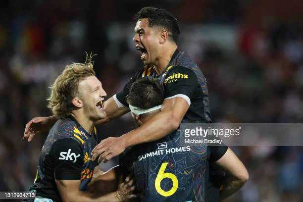 Anton Lienert-Brown of the Chiefs celebrates with Mitchell Brown and Damian McKenzie during the round eight Super Rugby Aotearoa match between the...