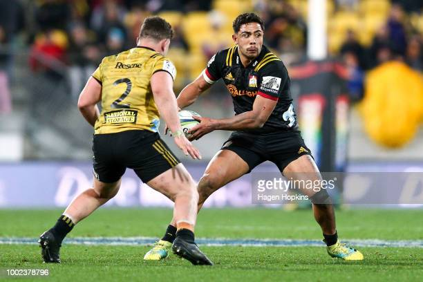 Anton LienertBrown of the Chiefs looks to pass under pressure from Ricky Riccitelli of the Hurricanes during the Super Rugby Qualifying Final match...