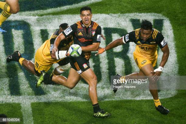 Anton LienertBrown of the Chiefs passes under pressure from Loni Uhila and Julian Savea of the Hurricanes during the round three Super Rugby match...