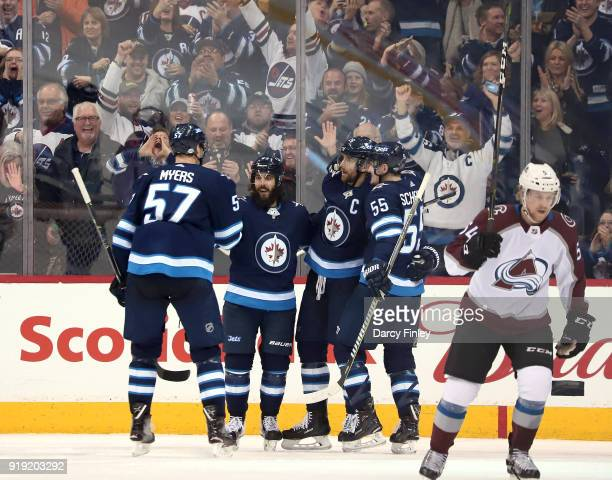 Anton Lindholm of the Colorado Avalanche skates away as Tyler Myers Mathieu Perreault Blake Wheeler and Mark Scheifele of the Winnipeg Jets celebrate...