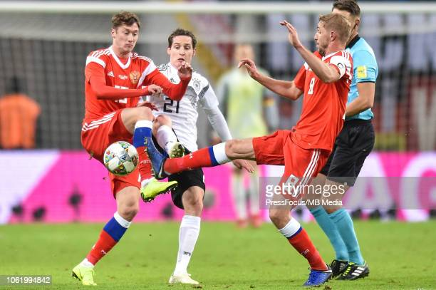 Anton Miranchuk and Iurii Gazinskii of Russia tackles Sebastian Rudy of Germany during International Friendly match between Germany and Russia at Red...