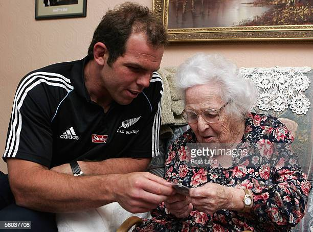Anton Oliver presents 95yearold Enid Williams with an All Black pin during a visit to Enid's home October 31 2005 in Cardiff Wales Enid's father was...