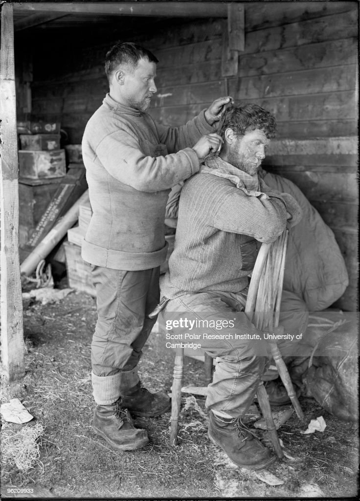 Anton Omelchenko cuts Patrick Keohane's hair at their camp in the Ross Dependency of Antarctica, during Captain Robert Falcon Scott's Terra Nova Expedition to the Antarctic, January 1912.