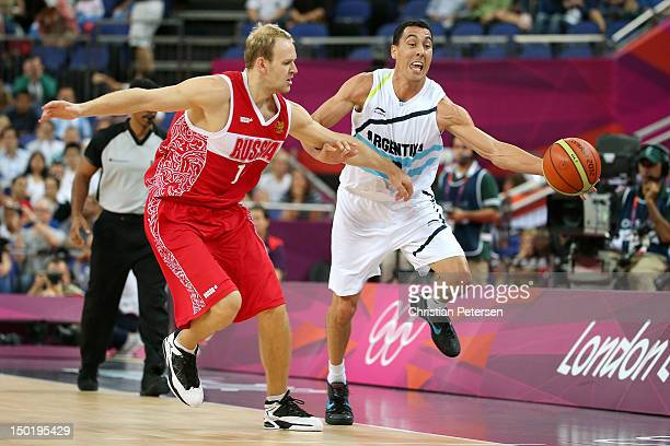 Anton Ponkrashov of Russia competes for a loose ball with Pablo Prigioni of Argentina during the Men's Basketball bronze medal game between Russia...