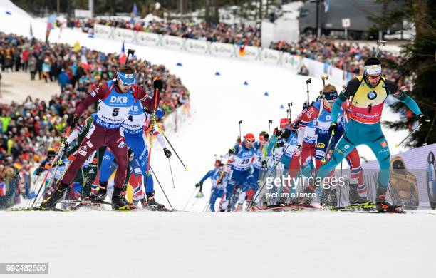 Anton Schipulin of Russia and Martin Fourcade of France lead the field as they come up the hill to the shooting range during the men's mass start...