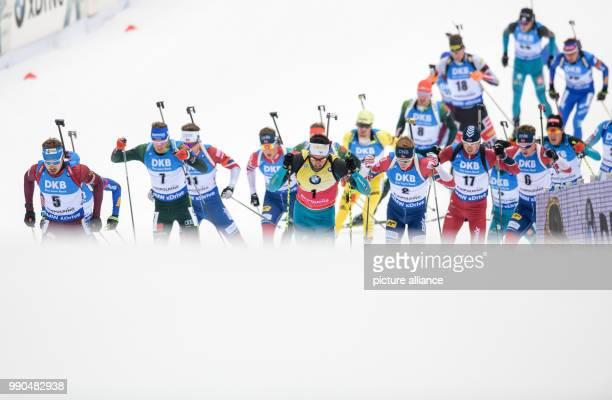 Anton Schipulin of Russia Simon Schempp of Germany and Martin Fourcade of France lead the field as they come up the slope to the shooting range...