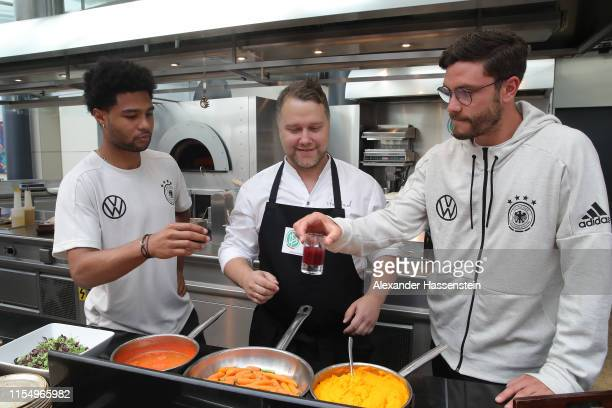 Anton Schmaus, chef of Germany smiles with players Serge Gnabry and Jonas Hector prior to a press conference of the German national team at Hyatt...