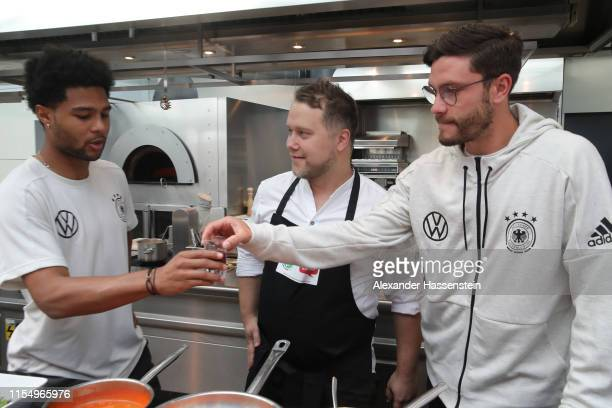 Anton Schmaus, chef of Germany taste a drink with players Serge Gnabry and Jonas Hector prior to a press conference of the German national team at...