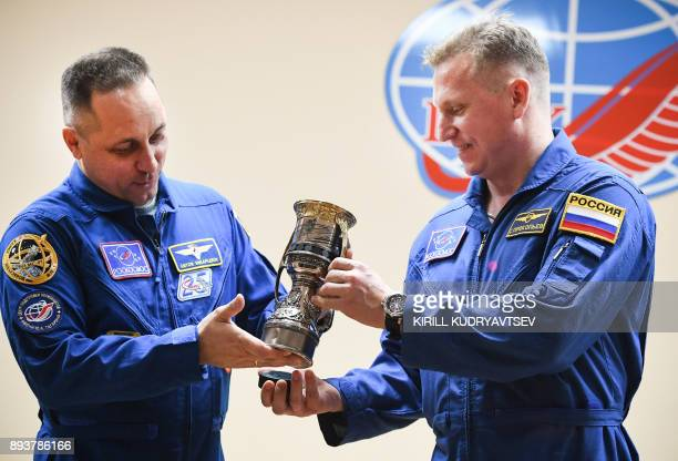 Anton Shkaplerov of Roscosmos and his back up crew member Sergei Prokopiev pose with a replica of the Gagarin Cup the trophy of the Russia's...