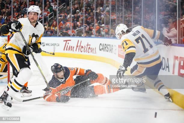 Anton Slepyshev of the Edmonton Oilers battles against Brian Dumoulin and Evgeni Malkin of the Pittsburgh Penguins at Rogers Place on November 1 2017...