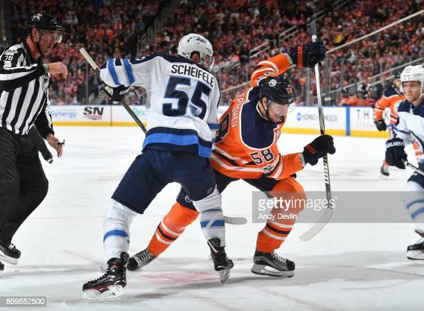 Anton Slepyshev of the Edmonton Oilers battles for the puck against Mark Scheifele of the Winnipeg Jets on October 9 2017 at Rogers Place in Edmonton...