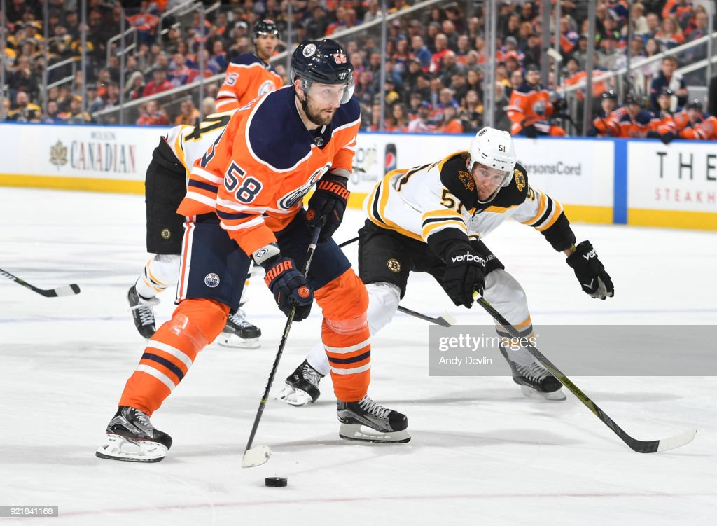Anton Slepyshev #58 of the Edmonton Oilers skates with the puck while being pursued by Ryan Spooner #51 of the Boston Bruins on February 20, 2018 at Rogers Place in Edmonton, Alberta, Canada.