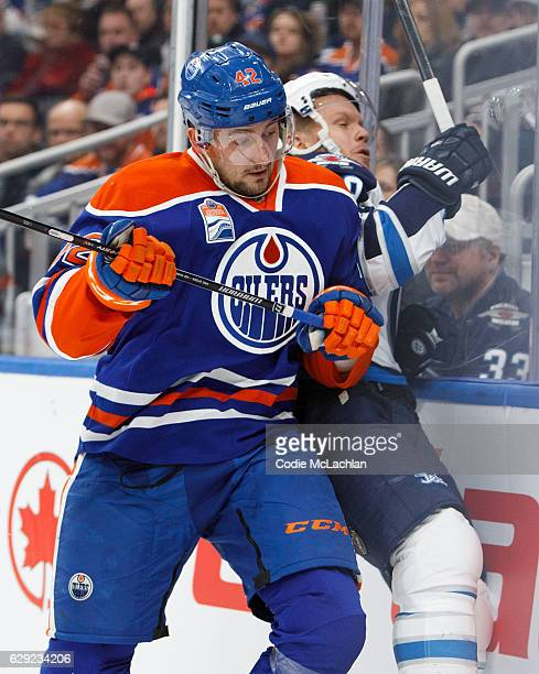 Anton Slepyshev of the Edmonton Oilers takes Toby Enstrom of the Winnipeg Jets into the boards on December 11 2016 at Rogers Place in Edmonton...