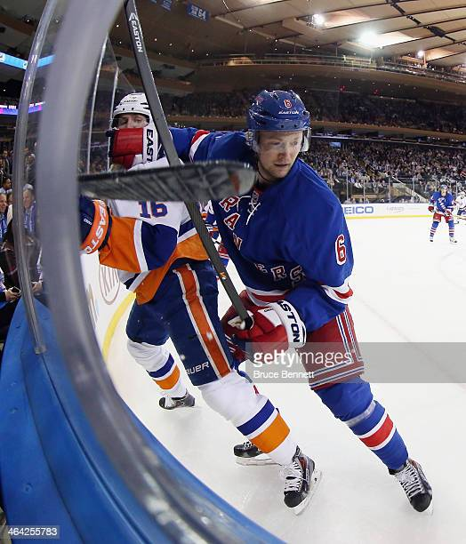 Anton Stralman of the New York Rangers gets the glove up on Peter Regin of the New York Islanders during the first period at Madison Square Garden on...