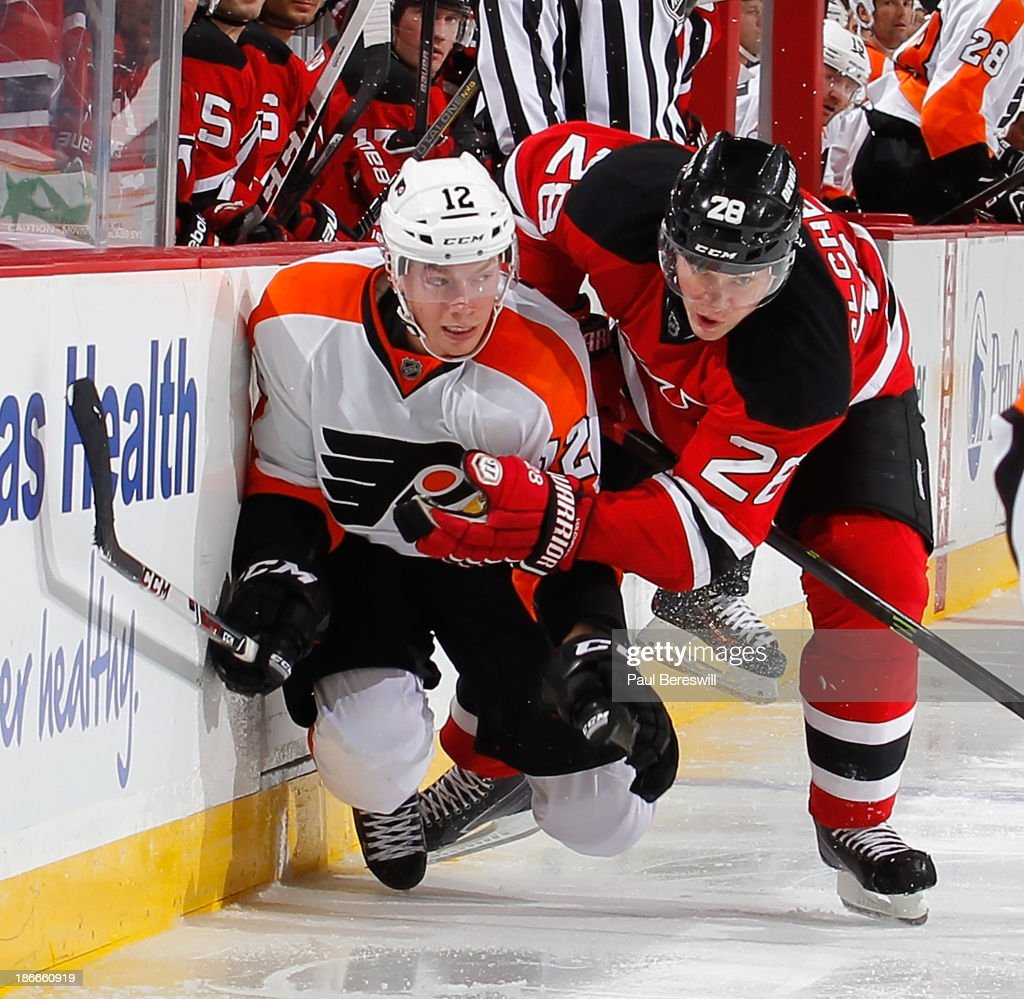 Anton Volchenkov #28 of the New Jersey Devils checks Michael Raffl #12 of the Philadelphia Flyers during the third period of an NHL hockey game at Prudential Center on November 2, 2013 in Newark, New Jersey.