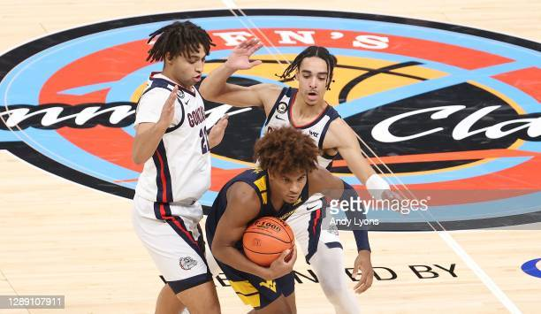 Anton Watson and Andrew Nembhard of the Gonzaga Bulldogs defend Miles McBride of the West Virginia Mountaineers during the Jimmy V Classic at Bankers...