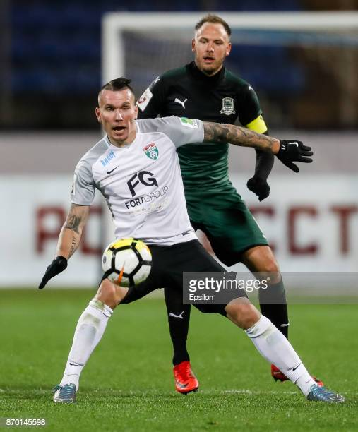 Anton Zabolotny of FC Tosno and Andreas Granqvist of FC Krasnodar vie for the ball during the Russian Football League match between FC Tosno and FC...