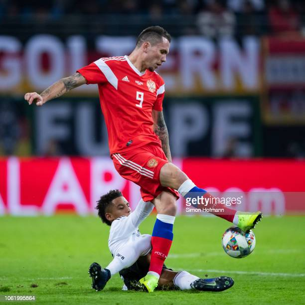 Anton Zabolotny of Russia is tackled by Thilo Kehrer of Germany during the International Friendly match between Germany and Russia at Red Bull Arena...