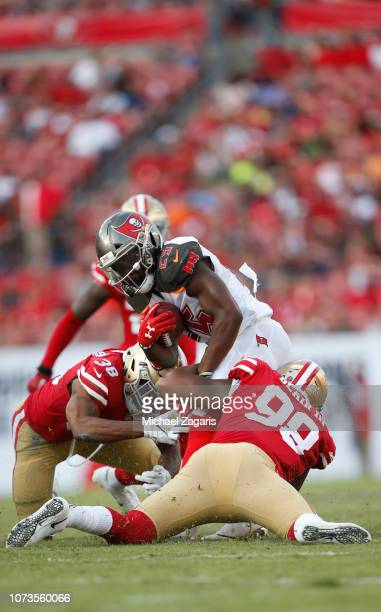 Antone Exum Jr #38 and DeForest Buckner of the San Francisco 49ers stop Peyton Barber of the Tampa Bay Buccaneers during the game at Raymond James...