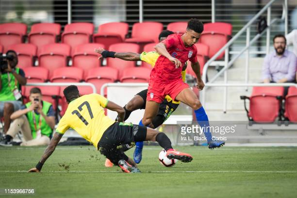 Antonee Robinson of the United States barrels toward the goal against Damion Lowe of Jamaica and Alvas Powell of Jamaica during the International...