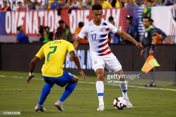 Antonee Robinson of USA fights for the ball with Douglas Costa of Brazil during their friendly match at MetLife Stadium on September 7 2018 in East...